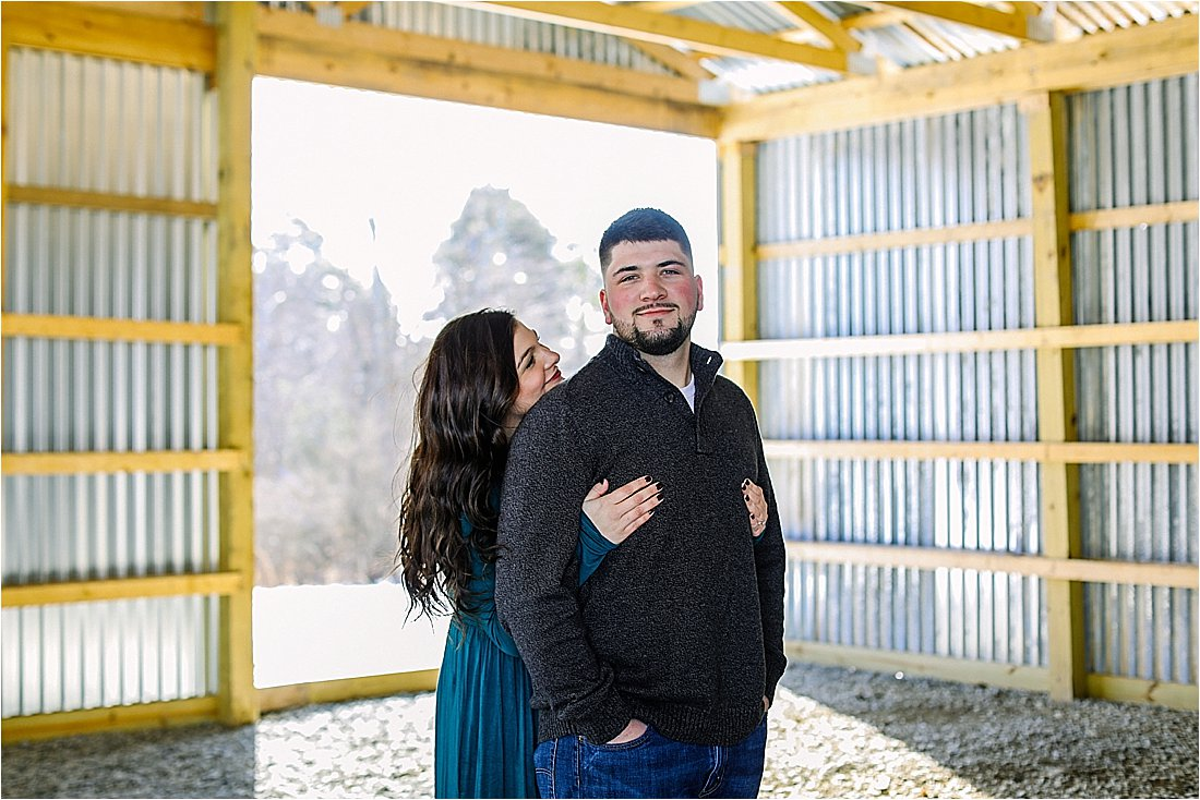 engaged couple have photos taken in the pole barn on his property in the winter