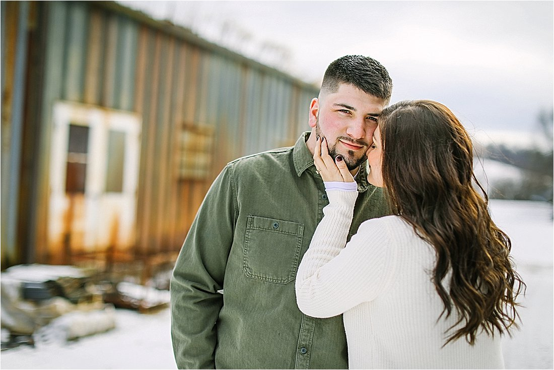 fiance kissing him on the cheek in the snow