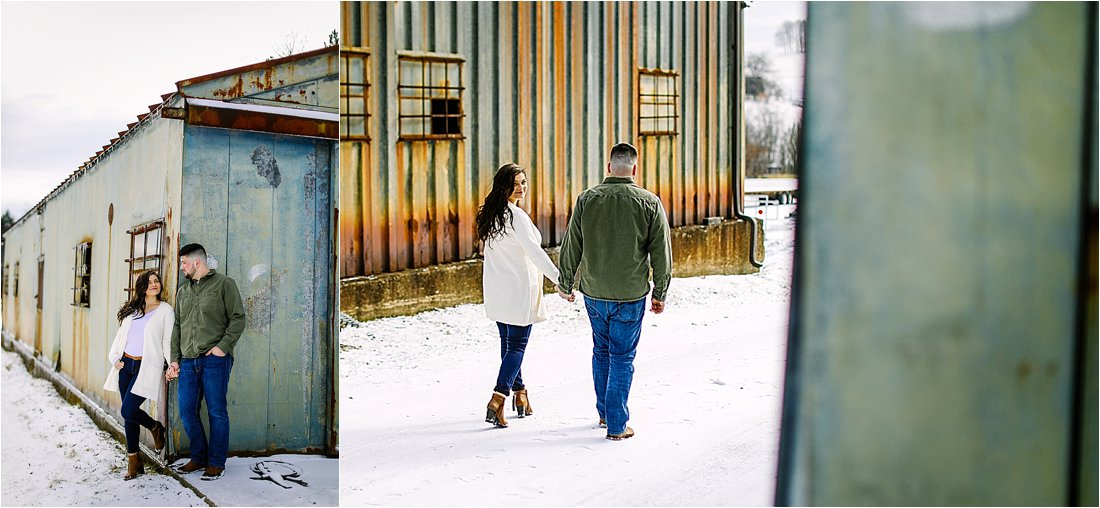 engaged couple walking away in the snow towards a rusted building