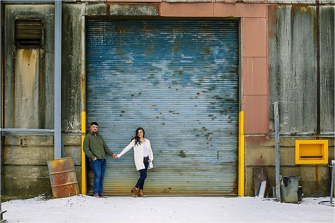 engaged couple in front of peeling steel painted garage door
