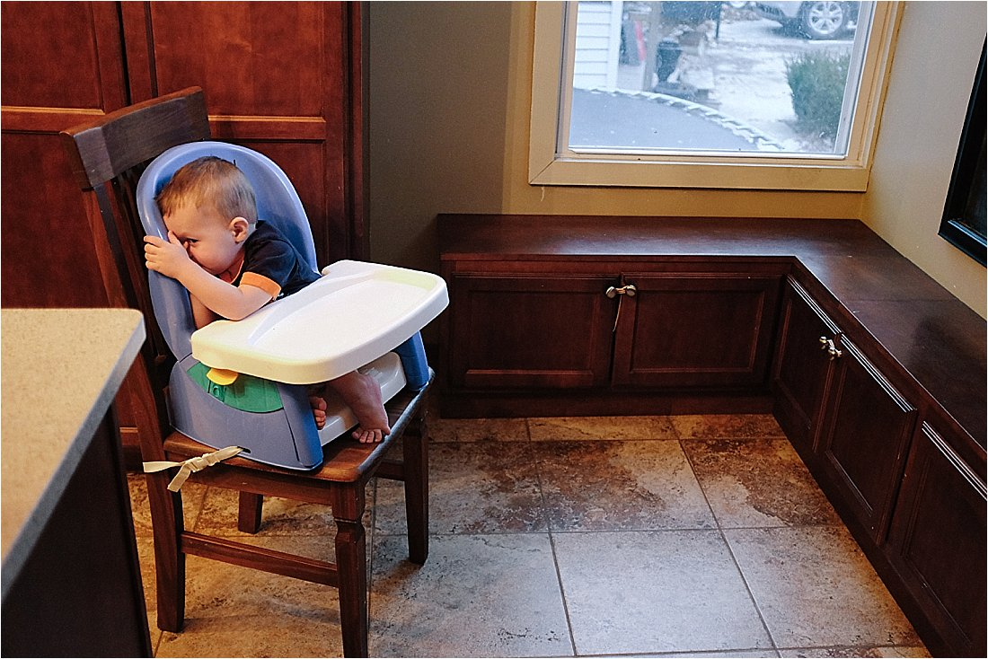 toddler being shy in his high chair