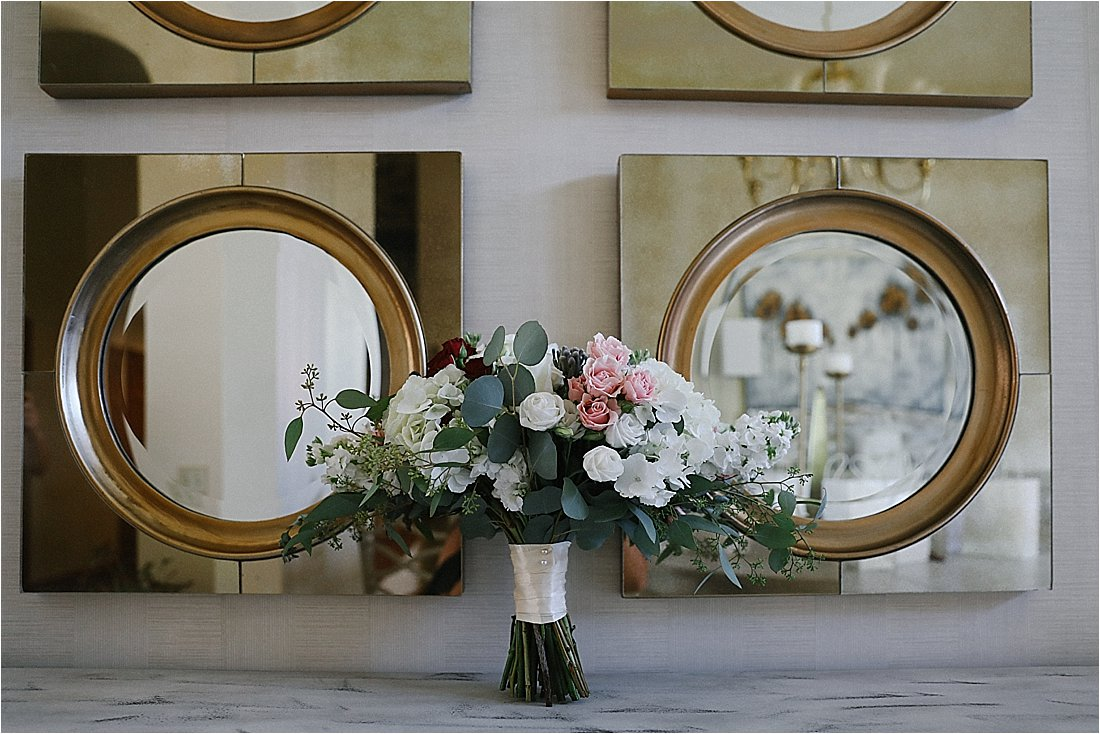 bridal bouquet in front of gold mirros