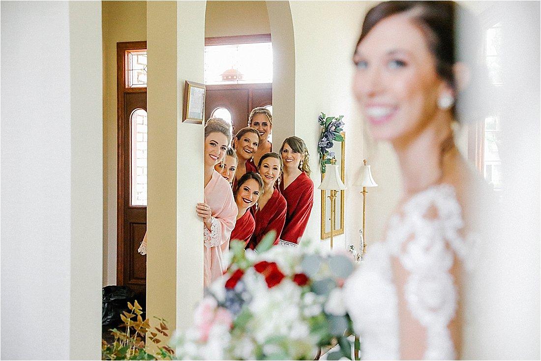 bridesmaids peeking thru the doorway at the bride