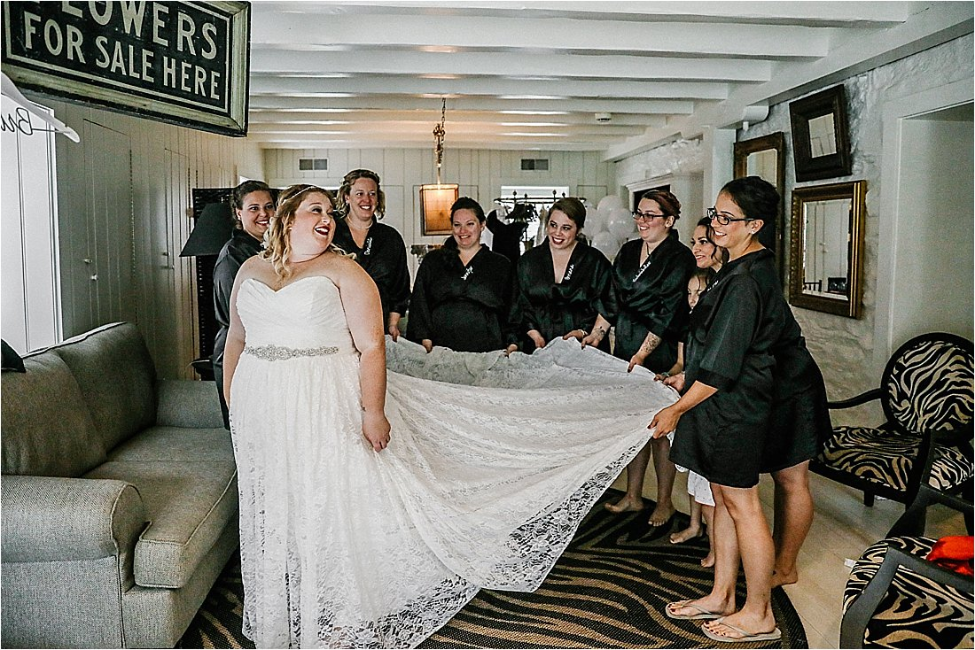 bridesmaids helping the bride get into her white wedding dress