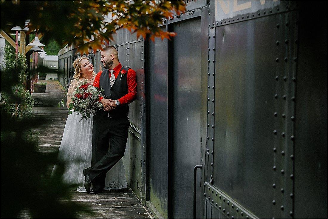 bride and groom near a train car
