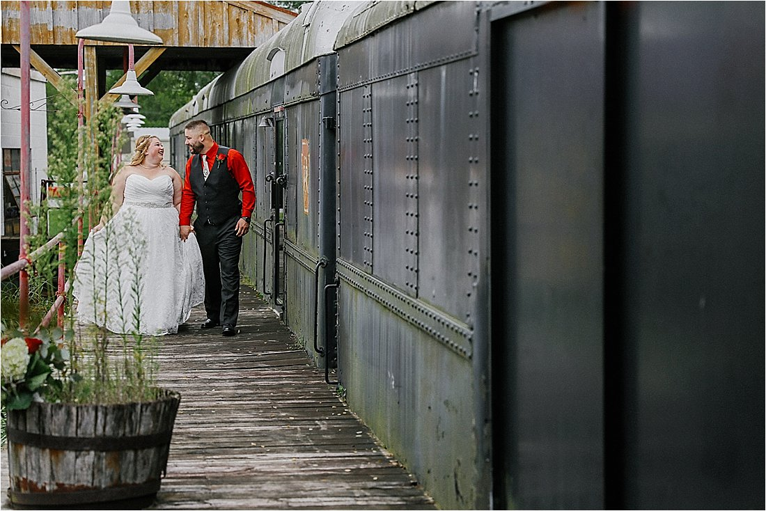 bride and groom walking near a train car