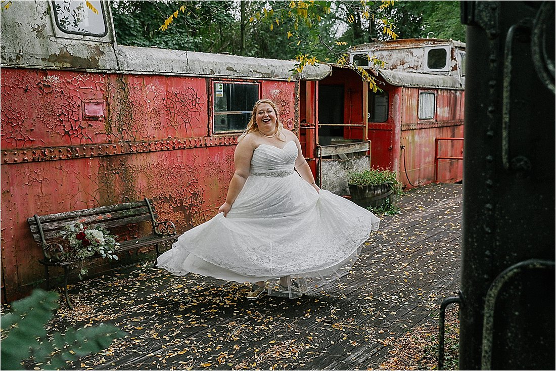 bride twirling her dress on a red train car