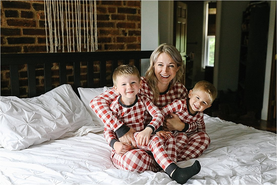 mom and sons jumping on the bed with christmas jammies
