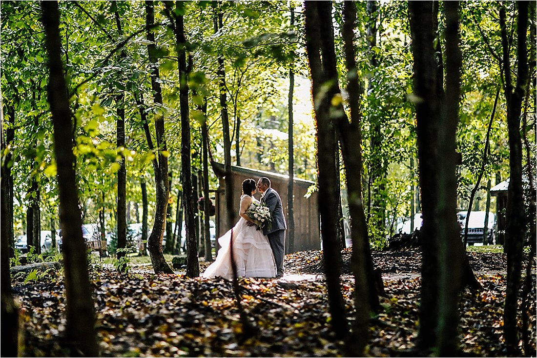 bride and groom kissing in between the trees with the sun