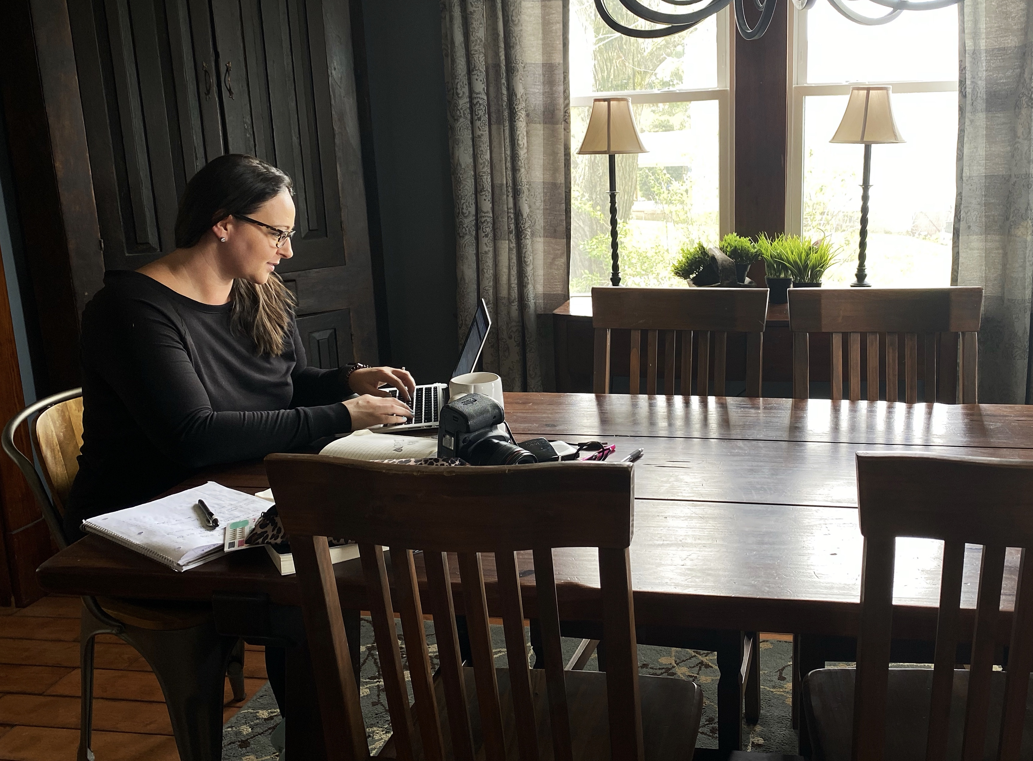 women working from a laptop at the dining room table